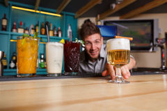 Young Barman offers non-alcoholic cocktails in night club bar Royalty Free Stock Image
