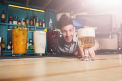 Young Barman offers non-alcoholic cocktails in night club bar Royalty Free Stock Photography