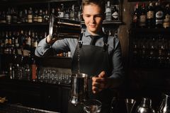 Young barman pouring a clear alcoholic drink on the bar counter Royalty Free Stock Photo