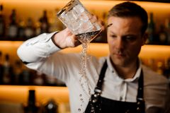 Young barman pouring water from a glass with ice cubes stock images