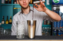 Young Barman`s making cocktail, pouring alcohol into glass Royalty Free Stock Images