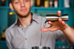 Young Barman's making shot cocktail, pouring alcohol into glass. Barman's hands in bar interior making alcohol shot cocktail. Professional bartender at work in royalty free stock image
