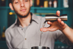 Young Barman's making shot cocktail, pouring alcohol into glass. Barman's hands in bar interior making alcohol shot cocktail. Professional bartender at work in stock images