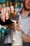 Young Barman`s making shot cocktail, pouring syrup into glass. Barman`s hands in bar interior making alcohol shot cocktail. Professional bartender at work in bar royalty free stock image