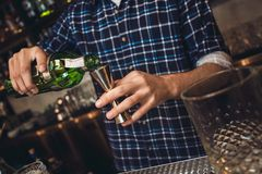 Young bartender standing at bar counter pouring whiskey into jigger close-up royalty free stock photos