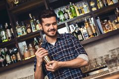Young bartender standing at bar counter shaking shaker smiling thoughtful royalty free stock photos