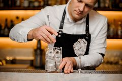 Young barman stirring ice cubes in a glass Royalty Free Stock Images