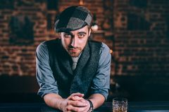 Young bartender enjoying a night in bar, having an alcoholic drinks at the counter. Handsome bartender enjoying a night in bar, having an alcoholic drinks at the royalty free stock photos