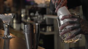 Young bartender guy with tattoos putting ice cubes in a cocktail