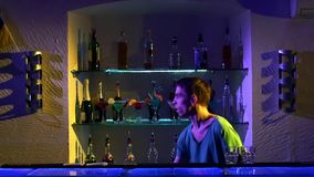 Young bartender making tricks with two glasses and stock footage