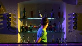 Young bartender making tricks with two glasses stock footage