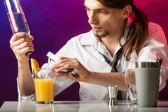 Young bartender pouring beverages. Alcohol liquor drinking party relax bartending concept. Young bartender pouring beverages. Male barman prepares cocktail in Stock Photography