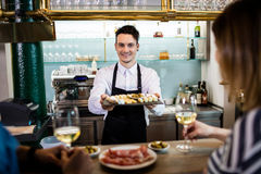 Young bartender serving food to customers at counter Royalty Free Stock Photography