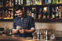 Young bartender standing at bar counter counting salary happy stock photo