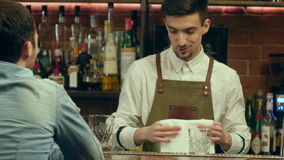 Young bartender talking and smiling to a male visitor stock video