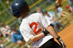 Young Baseball Player on Base. Little League player who made a hit waiting on first base for his chance to score royalty free stock photo