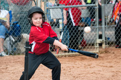 Young baseball player hitting ball off a tee