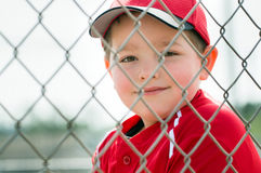 Young baseball player sitting in dugout. Young baseball player in uniform sitting in dugout royalty free stock photos