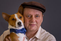 Young basenji dog wearing blue kerchief and its mature master wearing brown cap Royalty Free Stock Photography