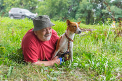 Young Basenji and its senior master lying an ambush Royalty Free Stock Photo