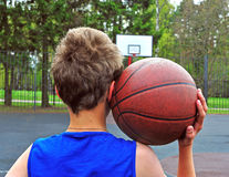 Young basketball player with a ball on his shoulder Stock Photo