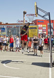 A young basketball player performs a throw to the slam dunk cont Royalty Free Stock Image