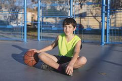 Young basketball player sitting on the court