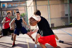 Young basketball players playing with energy. In a urban place Royalty Free Stock Images