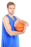 Young basketball pro holding a ball Stock Images
