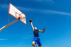 Young Basketball street player making slam dunk Royalty Free Stock Image