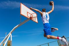 Young Basketball street player making slam dunk.  Royalty Free Stock Photo