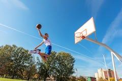 Young Basketball street player making slam dunk Stock Photo
