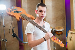 Young bass player with tattoo standing with guitar. On his shoulder in the studio Royalty Free Stock Photos