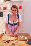 Young Bavarian girl in dirndl stands biscuits from a dough. Royalty Free Stock Photography