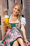 Young bavarian oktoberfest blonde woman in a dirndl dress with beer Royalty Free Stock Photos