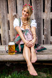 Young bavarian oktoberfest blonde woman in a dirndl dress with beer Royalty Free Stock Images