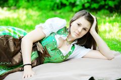 Young woman in dirndl lying on blanket in park royalty free stock photo