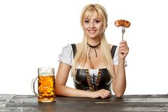 Young bavarian woman in dirndl sitting at table with beer on white background. Oktoberfest royalty free stock image