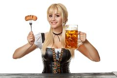 Young bavarian woman in dirndl sitting at table with beer on white background. Oktoberfest royalty free stock photo