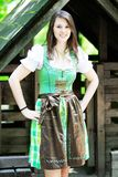 Young woman wearing a dirndl standing at wooden lodge royalty free stock images