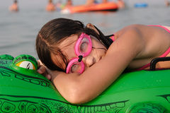 Young at beach. Young girl with diving goggles relax on floater crocodile at the beach Stock Images