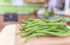 Young beans on the board for cutting. Stock Photo