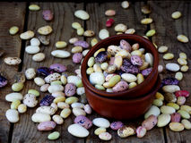Young beans of different varieties and colors in clay bowl on a wooden background. Stock Photos
