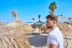 Young beard man in a beach with parasol. At summer Stock Photo