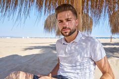 Young beard man in a beach under parasol. At summer Royalty Free Stock Images
