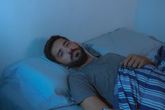 Young beard man lying on the bed awake Stock Images
