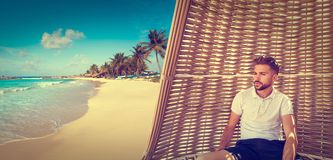Young beard man in parasol at tropical beach Royalty Free Stock Images