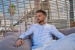 Young beard man relaxed in a beach parasol. Hammock at summer Stock Photography