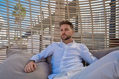 Young beard man relaxed in a beach parasol. Hammock at summer Stock Image