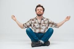 Young beard man sitting on floor meditate Royalty Free Stock Image